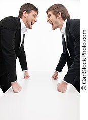 Men?s confrontation. Two angry young business people standing face to face and holding their fists at the table while isolated on white