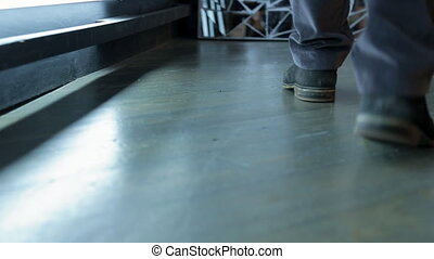Men's feet in boots go along the gray floor and stop at the...