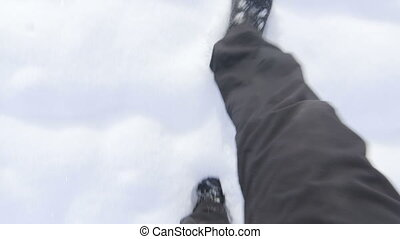 Men's feet walking on the snow POV