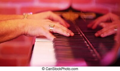 Men's fingers are sorted on the keys of the piano. Evening...