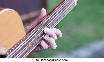 Men's Fingers on odd - Female hand holding guitar frets