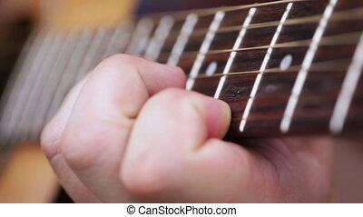 Men's Fingers on odds - Female hand holding guitar frets