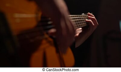 Men's fingers touch the acoustic guitar strings. Close up -...