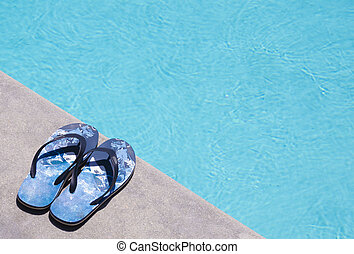 0d76f524 Flip flops by the pool. Pair of white flip flops by the pool on a ...