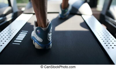Men's foot running on the treadmill in the gym