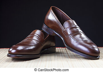 Mens Footwear Concepts. Pair of Stylish Brown Penny Loafer Shoes Placed on Straw Surface