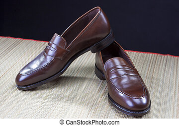 Mens Footwear Concepts. Pair of Stylish Brown Penny Loafer Shoes Placed on Straw Surface against Black.