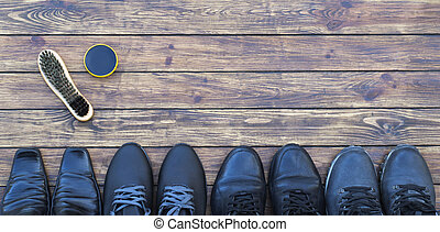 four pairs of different shoes on a wooden background, a shoe polish and a shoe brush. view from above