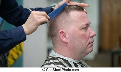 Men's haircut in Barbershop. Close-up of a master cut hair of scandinavian looking man with blond hair with scissors