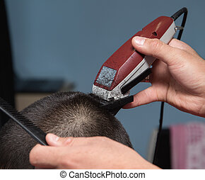 Men's haircut in the barber shop machine