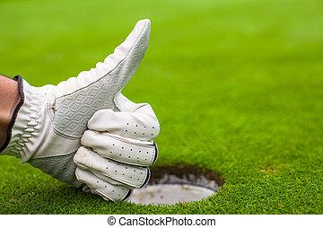 Men's hand in a glove golf shows OK near the hole