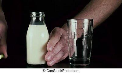 Men's hand pours milk into a glass