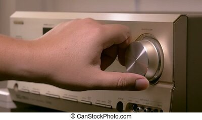 Men's hands are changing the volume in the amplifier of the...