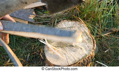 Men's hands chop firewood with an ax on a special stump on a background of beautiful green grass in the setting sun. Man chopping wood for the grill, fireplace or stove top view