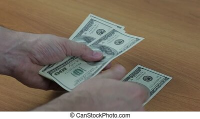 Men's hands counting cash dollar bills