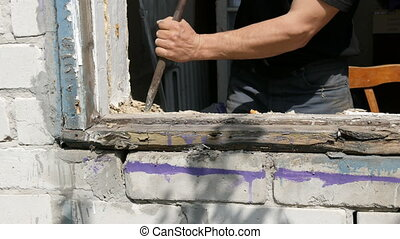 Men's hands dismantle the frames of an old rotten wooden ...