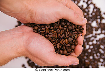 Men's hands hold a handful of coffee beans. Roasted coffee beans.