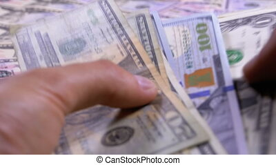 Men's Hands Hold a Pile of American Dollars against the...