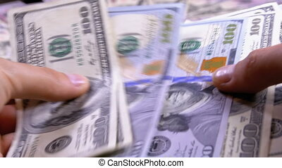 Men's Hands Hold a Pile of American Dollars against the Background of Rotating Money