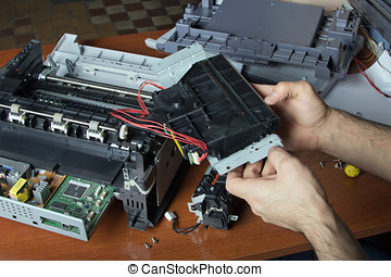 men's hands repairing laser printer