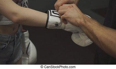 Men's hands tie a boxing glove closeup. Slow motion