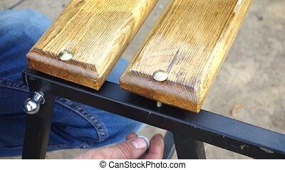 Men's hands tighten the nut.
