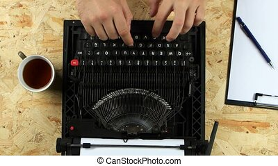 Men's hands type the text of the book on a typewriter. View from above