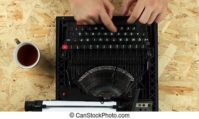 Men's hands type the text of the book on a typewriter. View...