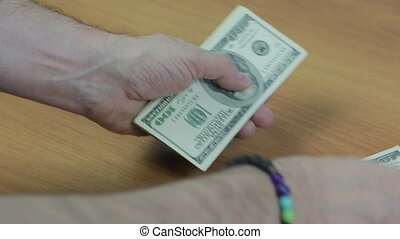 Men's hands with a bracelet count the bills