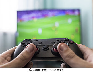 Men's hands with a joystick on the background of a TV, playing football, close-up