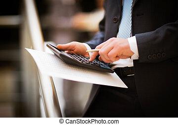 Men's hands with calculator.