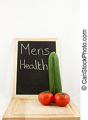 A chopping board with phallic salad, cucumber and tomato, with a chalk board in the background with the words 'mens health' all on white.
