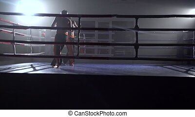 Mens in gloves beats a pear, in the ring there is a sparring...