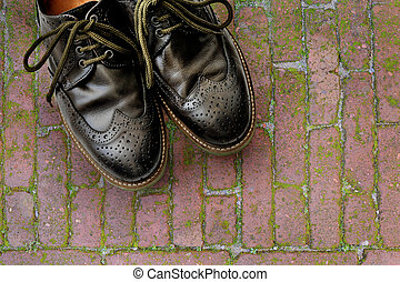 Men's leather shoes on the background of pavers