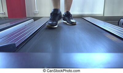 Men's legs run on the treadmill in the gym, lose weight,...
