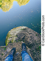 Men's legs stand on a stone in front of the lake.
