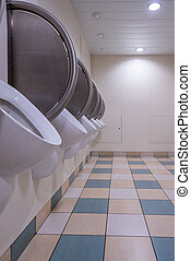 Men's public restroom with urinals on the wall and checkered floor.