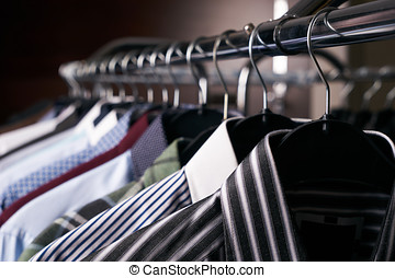 Mens shirts in different colors on hangers