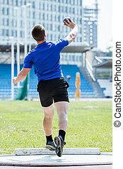 Men's shot put - Rear view of athlete in sportswear shot put...