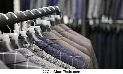 Men's suit at tailor's shop. Men's hands choose a jacket in...