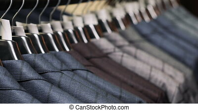 Men's suit at tailor's shop. Men's hands choose a jacket in their wardrobe. Male choosing