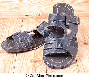 Men's summer sandals on a light wooden background