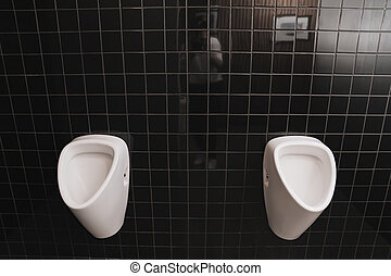men's toilet with urinal. toilet room with black ceramic tiles on the walls.