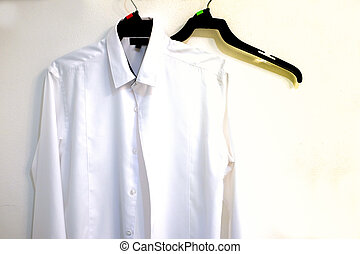 Men's white shirt hanging at the white wall