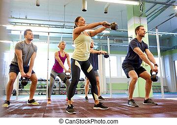 menschengruppe, mit, kettlebells, trainieren, in, turnhalle