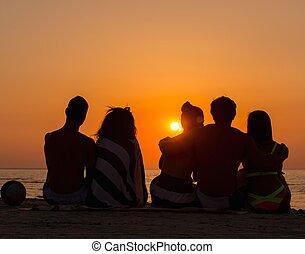 mensen zittende, nakomeling kijkend, silhouettes, zonsondergang strand