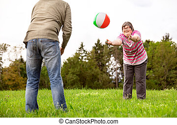 mental disabled woman is throwing a ball to a man