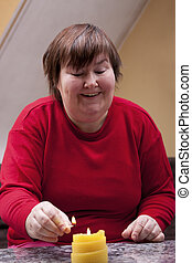 Mentally disabled woman lights a candle