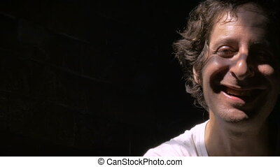 Mentally ill man, crazy or disturbed, laughing in dramatic lighting.