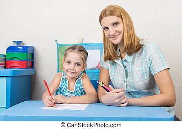 Mentor and five year old child draw with pencils sitting at the table